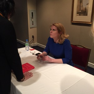 Amy Wilkinson, author of the Creator's Code,  listens carefully to people as they stop by to get their books autographed.